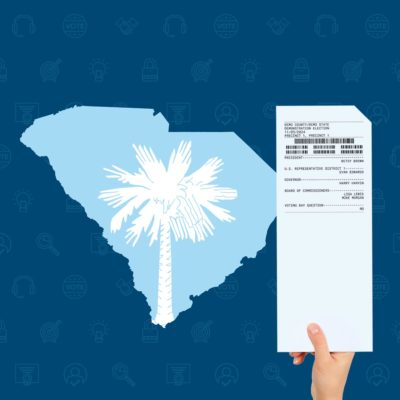 The shape of South Carolina with the palmetto from the state flag inset, next to a person's hand holding a voted paper ballot card.