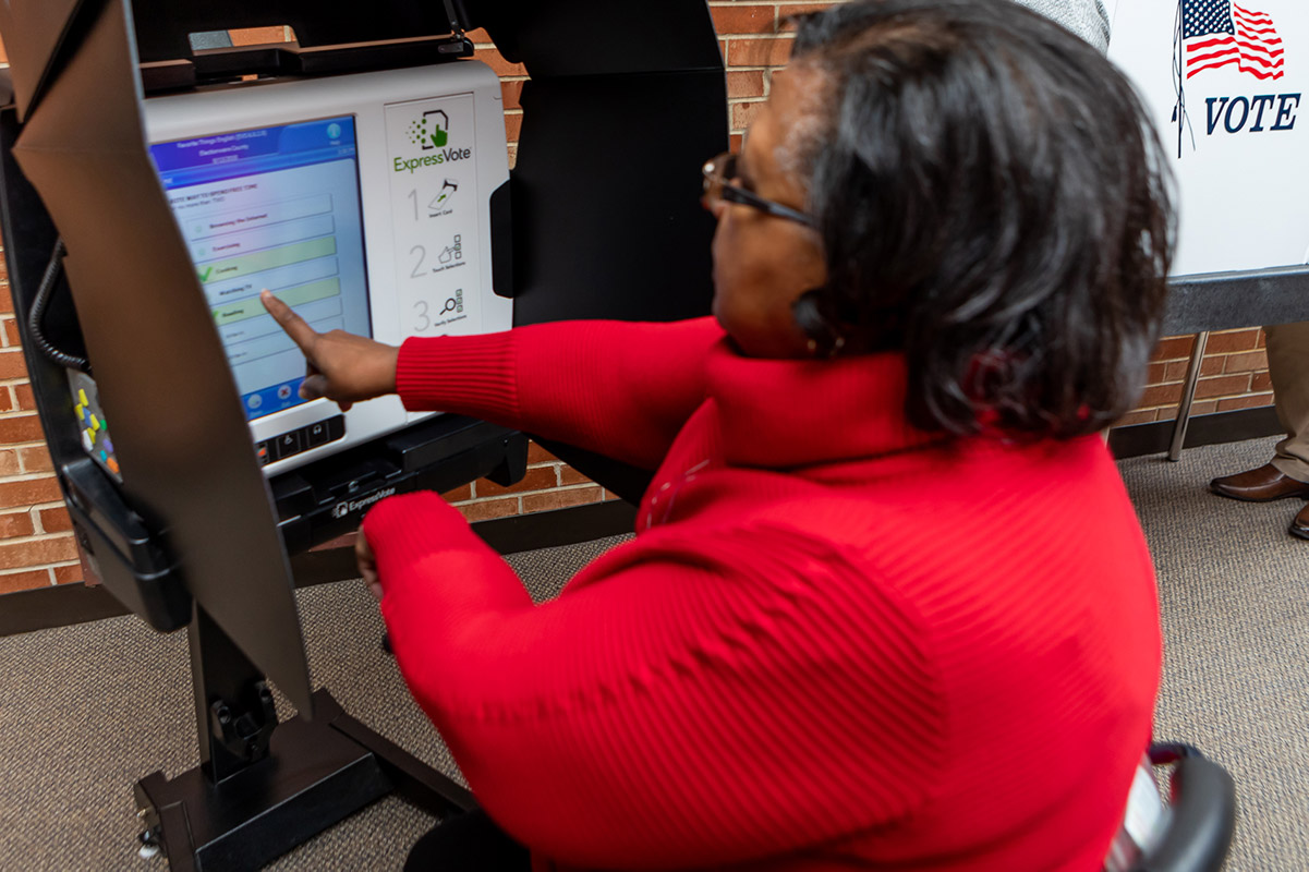 A seated voter using the ExpressVote with kiosk in the lowered position and privacy blinds