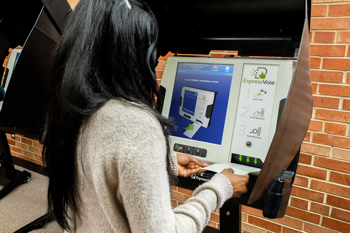 Voter entering an activation card into an ExpressVote kiosk in the standing position.